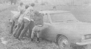 A car is pushed over by some kids (reenactment).